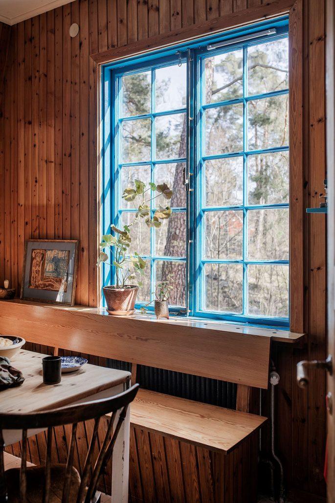 Fönsterspröjs målat i himmelsblått och furupanel i jugendvillan