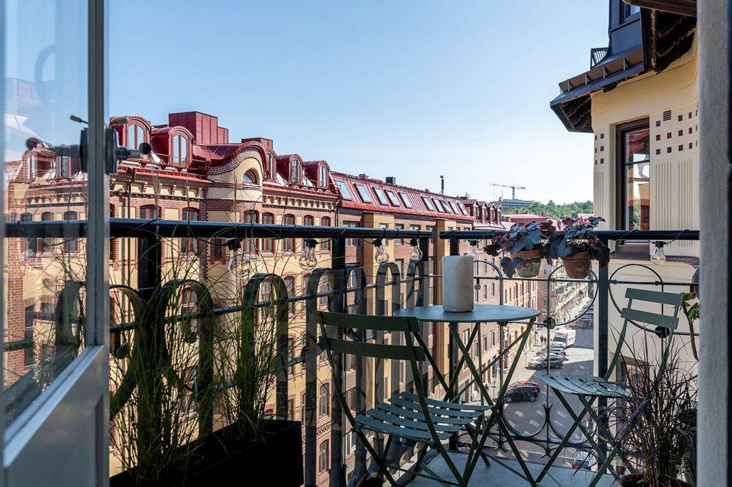 Insynsskyddad balkong med gröna bord och stolar.