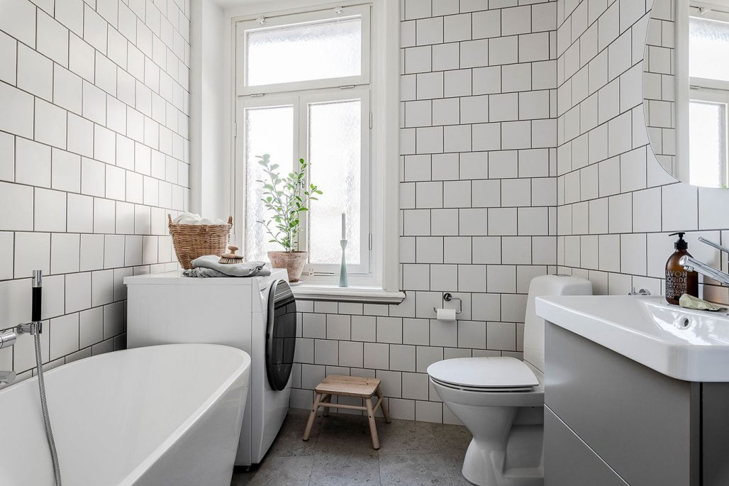 Badrum med matt vitt kakel och klinkerplattor från Norrvange Light Grey. Kommod från Vedum