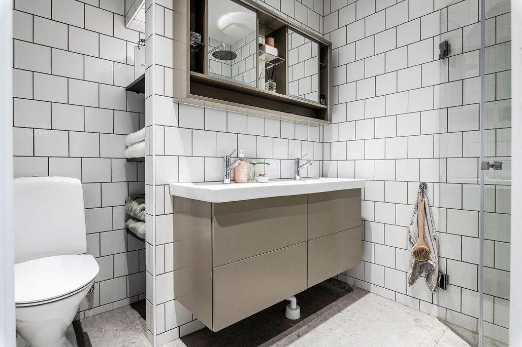 Badrum mett matt vitt kakel och klinkerplattor från Norrvange Light Grey. Spegelskåp från Vedum