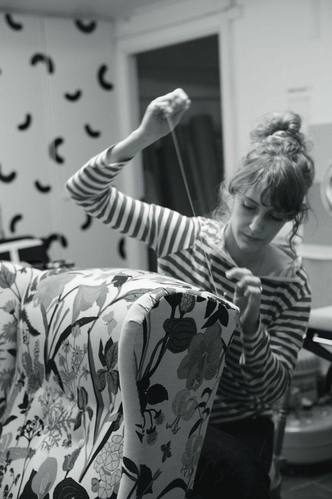 Möbeltapetserare Adina Asplund klär om en möbel